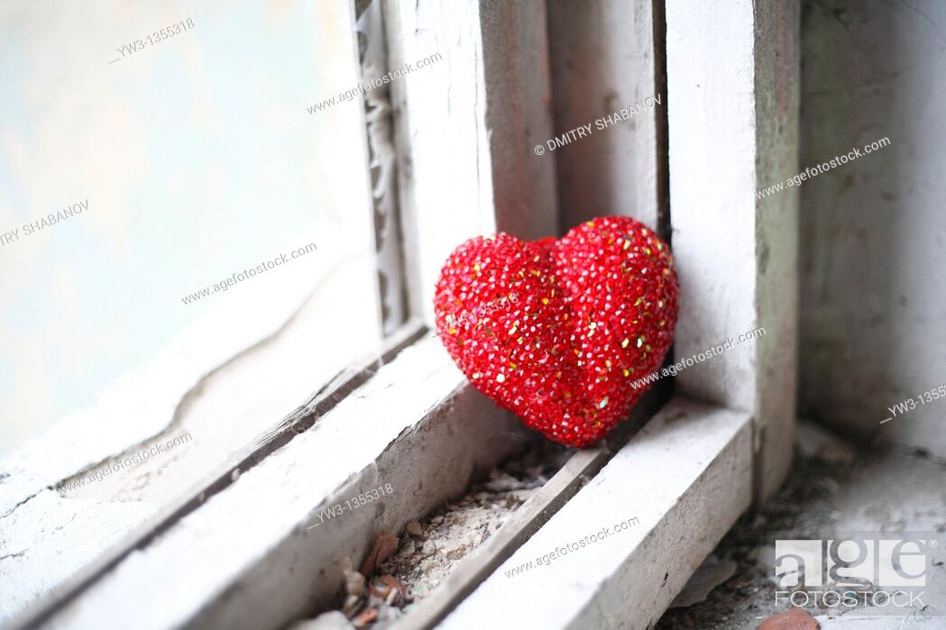 Stock Photo: loneliness concept - red heart on white obsolete windowsill.