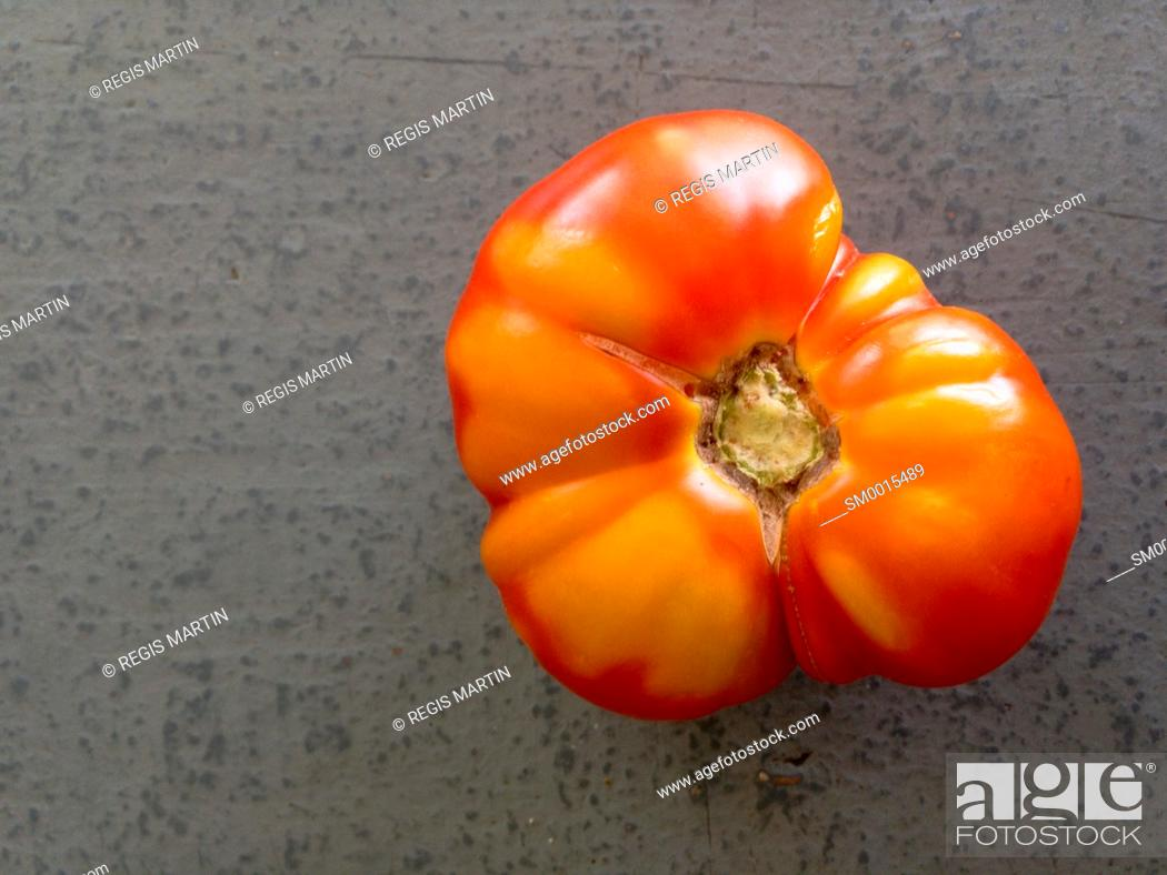 Stock Photo: A tomato viewed from above, on a grey background.