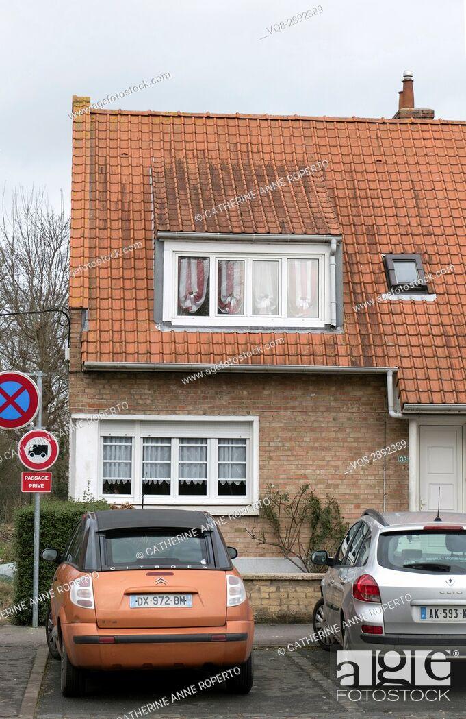Imagen: Terracotta tiled roof with corresponding terracota metallic car parked outside, Bergues, France.