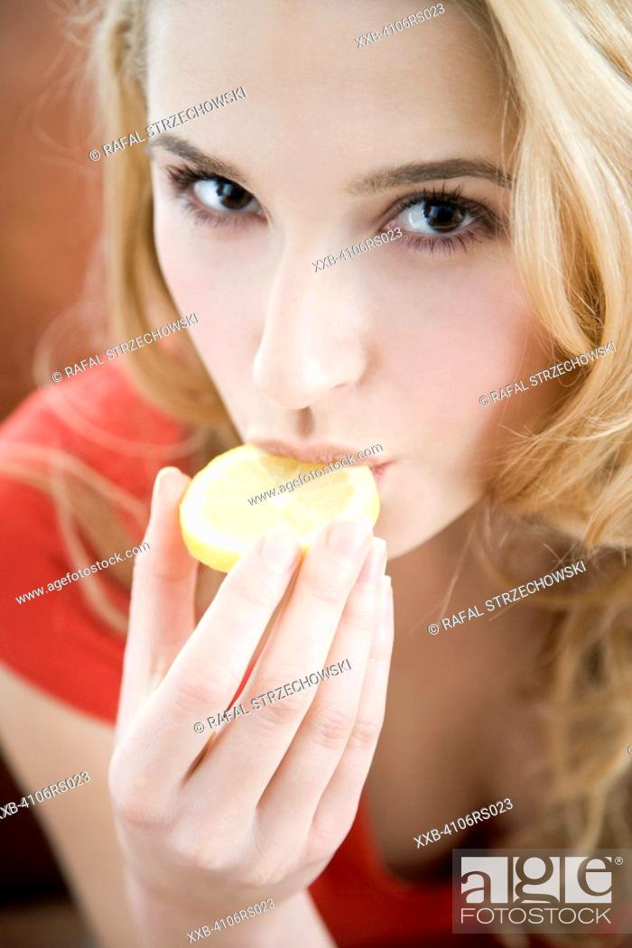Stock Photo: woman biting lemon.