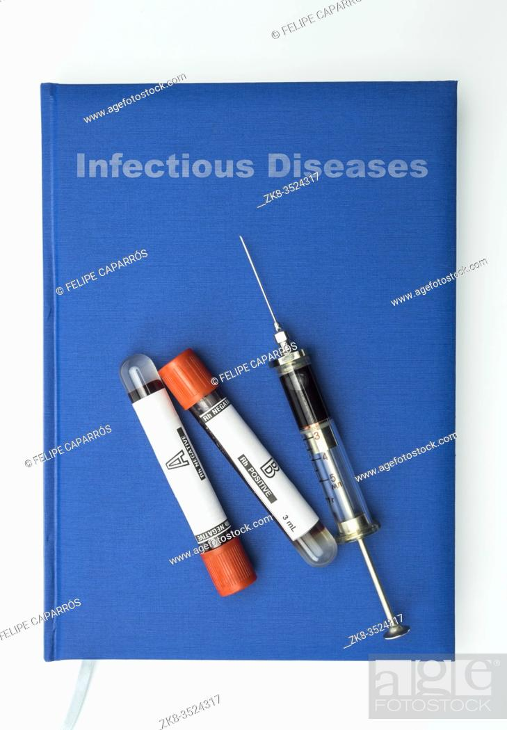 Stock Photo: Vintage Syringe and blood vials On A Book Of contagius diseases, Medical Concept.