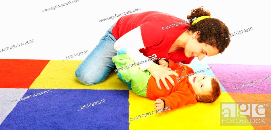 Stock Photo: Mother Play with her ten months old baby girl on a colored carpet.