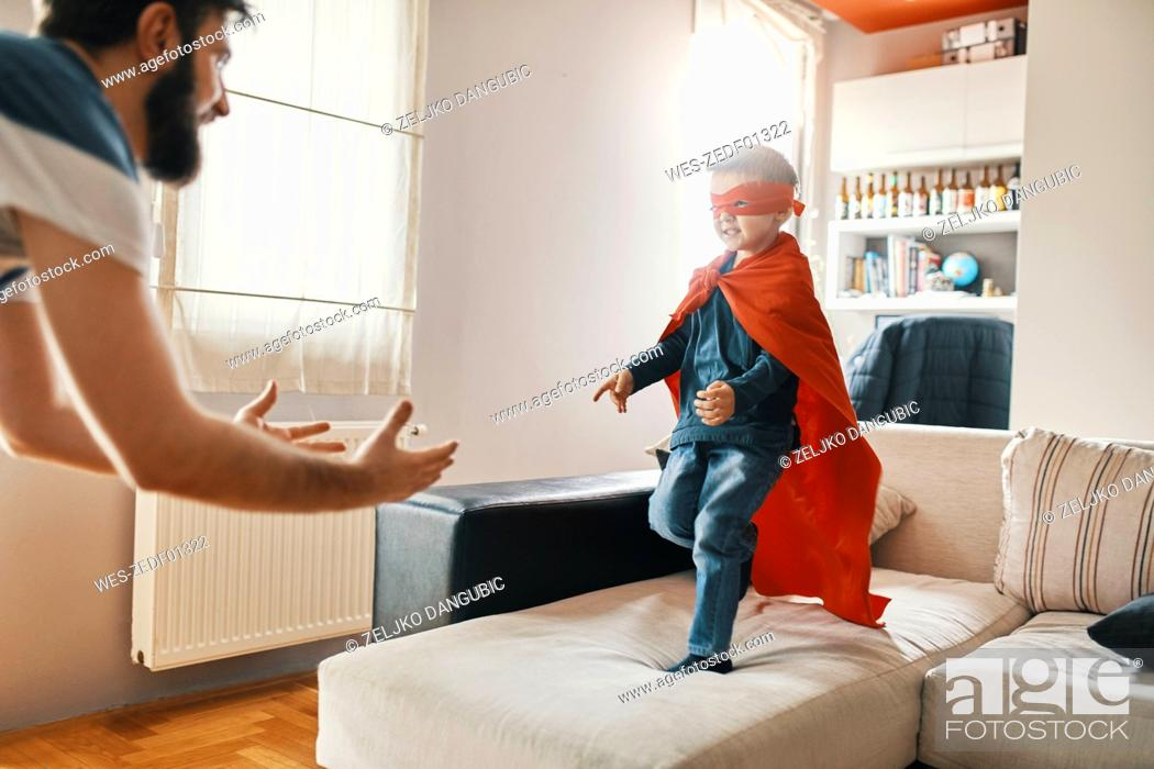 Stock Photo: Father playing with his little son dressed up as a superhero at home.