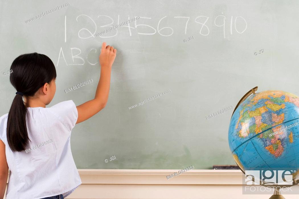 Stock Photo: Young girl writing on blackboard.