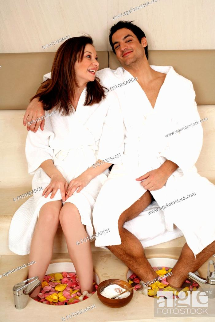 Stock Photo: A young couple enjoying a foot bath with rose petals.