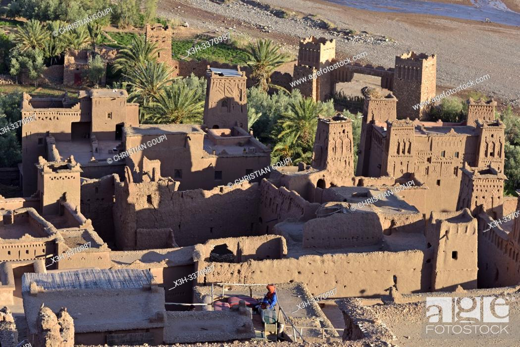 Stock Photo: man sitting on the terrace of a cafe overlooking the Ksar of Ait-Ben-Haddou, Ounila River valley, Ouarzazate Province, region of Draa-Tafilalet, Morocco.
