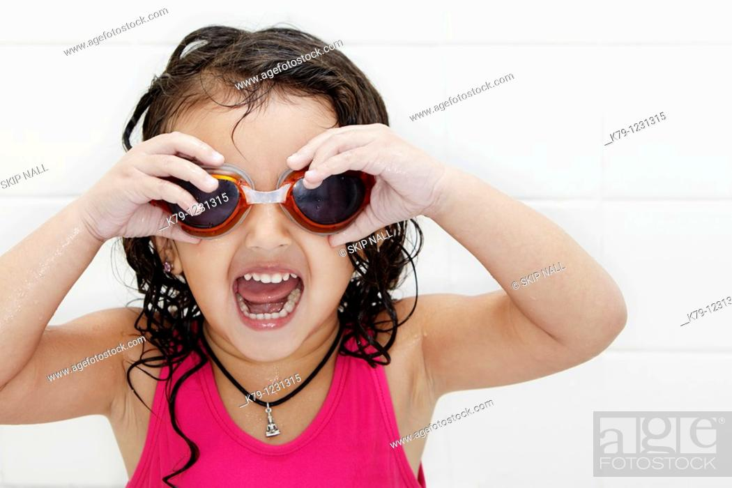 Stock Photo: Little girl in swim suit and swim goggles with excited look on her face.