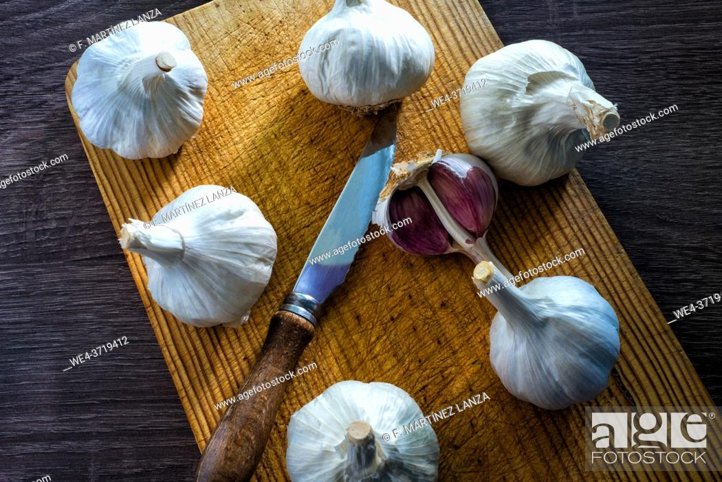 Imagen: white garlic with a knife on a board.