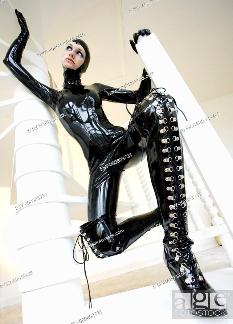 Stock Photo: woman in latex sitting on the stairs.