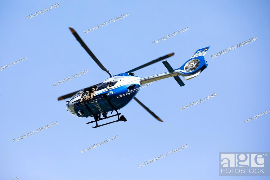 Stock Photo: 13 July 2020, Baden-Wuerttemberg, Oppenau: A police helicopter takes off from a sports field near Oppenau, which serves as a meeting point for the police.