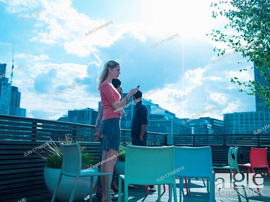 Stock Photo: Smiling men and women talking on urban balcony.