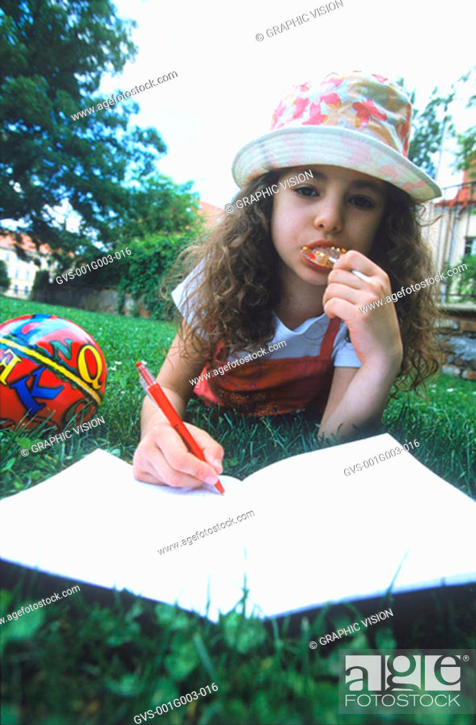 Stock Photo: Young girl lying down writing in a book.