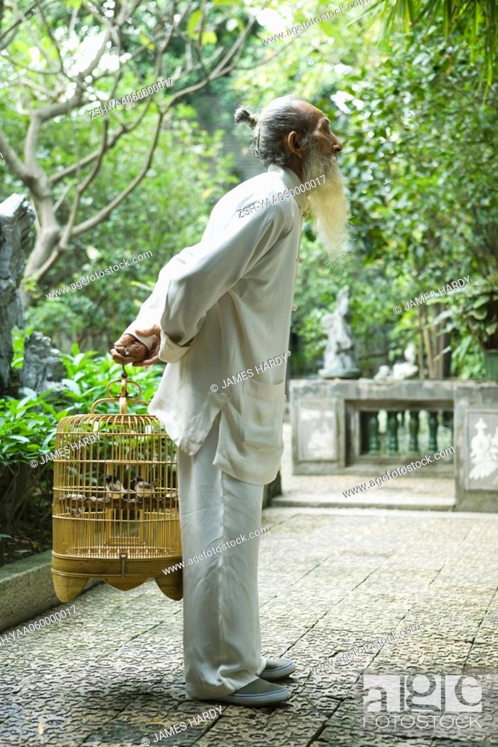Stock Photo: Elderly man in traditional Chinese clothing holding bird cage behind back.