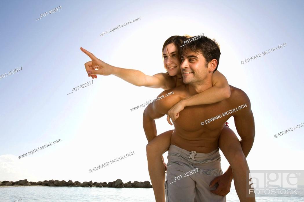 Stock Photo: Man giving woman a piggyback by sea.