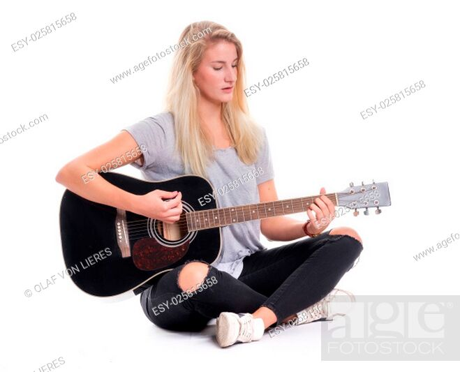 Stock Photo: young girl sitting cross-legged and playing guitar.