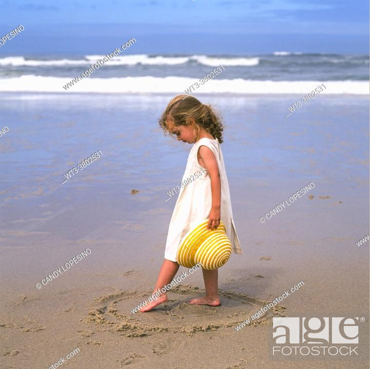 Stock Photo: Little three-year-old girl with hat in hand and foot playing in the sand on the beach on a sunny day by the sea.