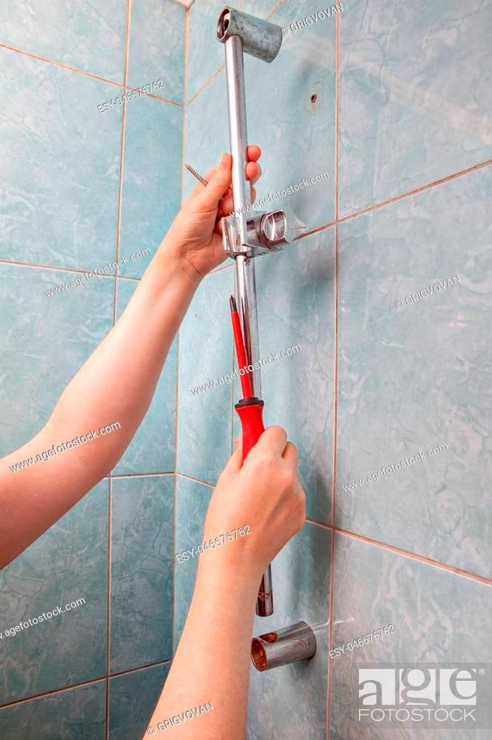 Stock Photo: Replace broken wall mounted vertical height adjustable shower bar slider rail holder, close-up of hands remove the faulty slide rail.