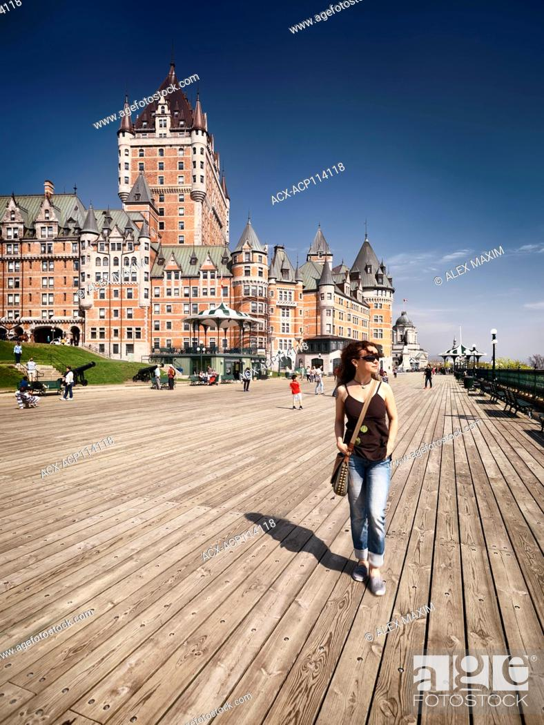 Stock Photo: Young woman walking alone on Dufferin terrace boardwalk with Fairmont Le Château Frontenac castle in the background, luxury grand hotel Chateau Frontenac.
