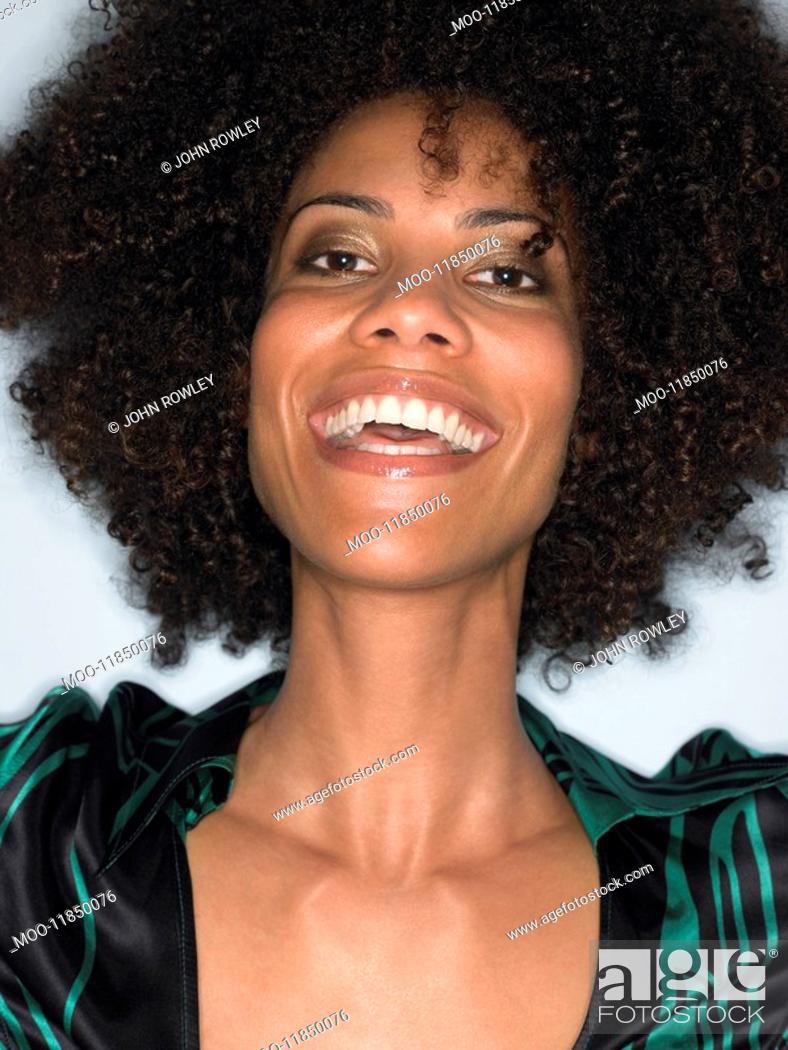 Stock Photo: Woman with afro smiling head and shoulders in studio.