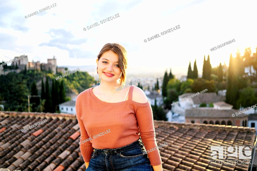 Stock Photo: Portrait of smiling woman with Alhambra in background, Granada, Spain.