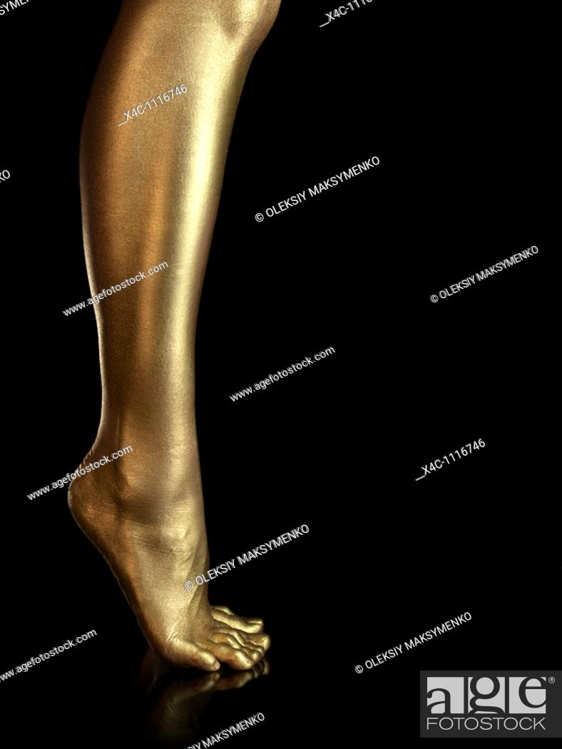 Stock Photo: Woman legs covered with gold  Isolated on black background.