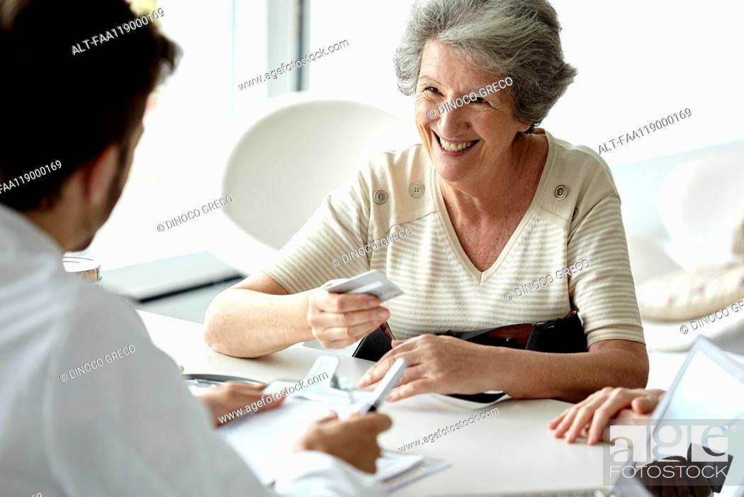 Stock Photo: Senior woman talking with doctor in clinic.