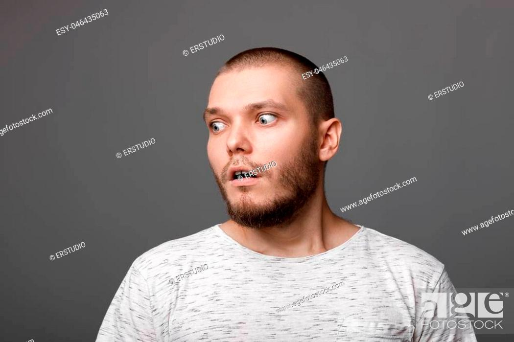 Stock Photo: portrait of surprised young man on gray backround.