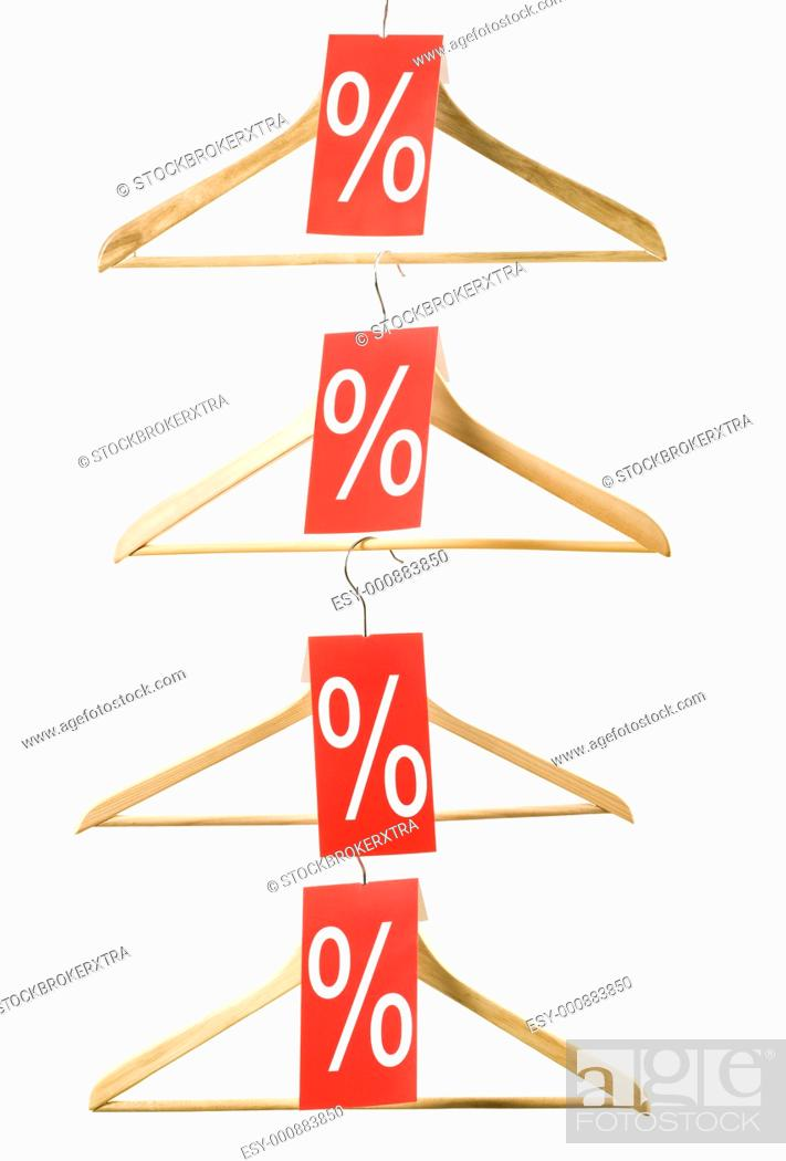 Stock Photo: Image of wooden hangers with sale discount red checks on white background.