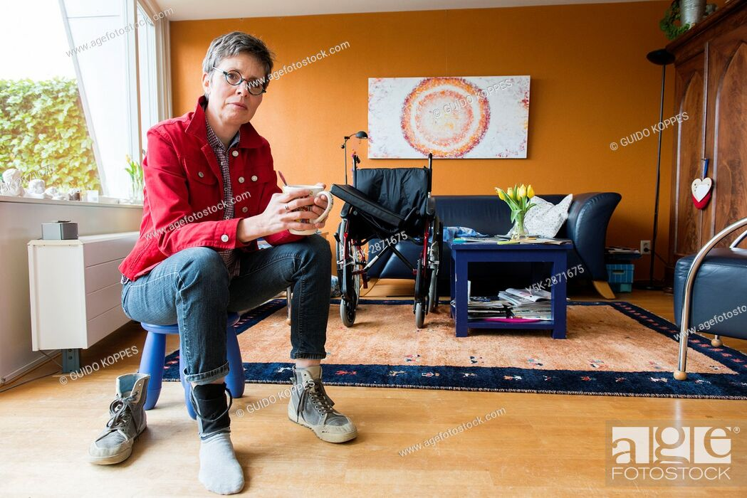 Stock Photo: Tilburg, Netherlands. Living room portrait of a mature adult woman suffering from Multiple Sclerosis sitting besides her unused wheelchair.