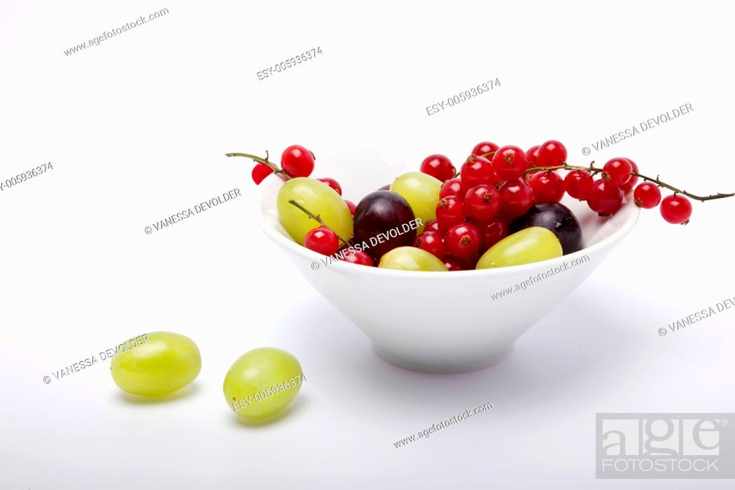 Stock Photo: Studio photograph of a white bowl with grapes and redcurrents on a white background.