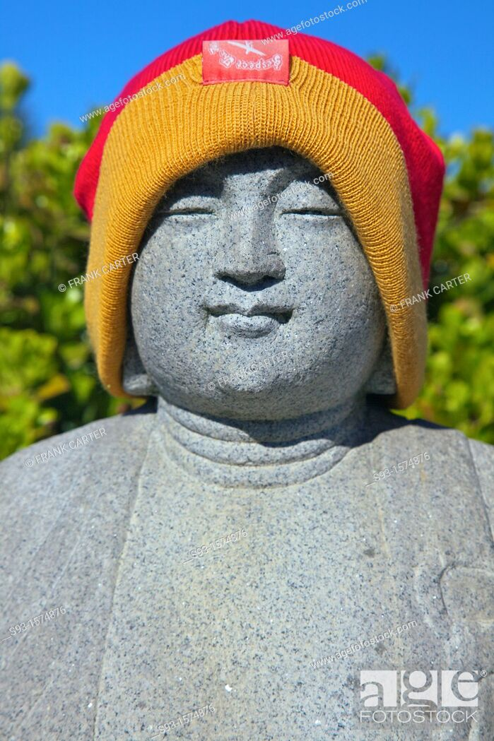 Stock Photo: A stone figure in a grave yard that someone has put a woven hat on.