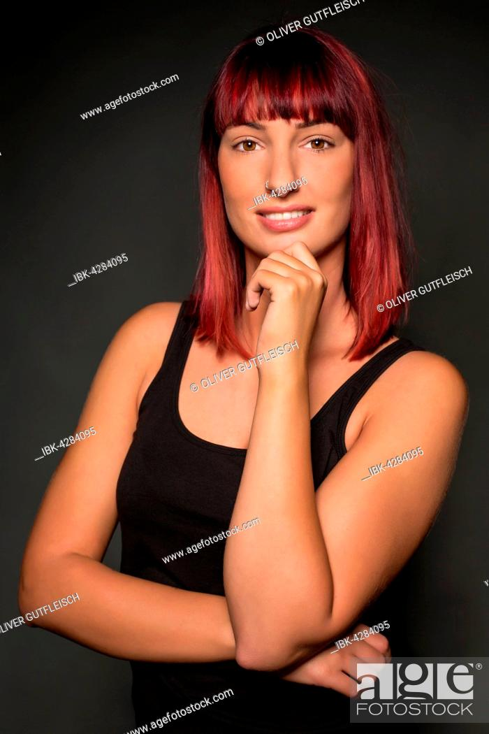 Stock Photo: Young woman with red hair, posing, looking into the camera.