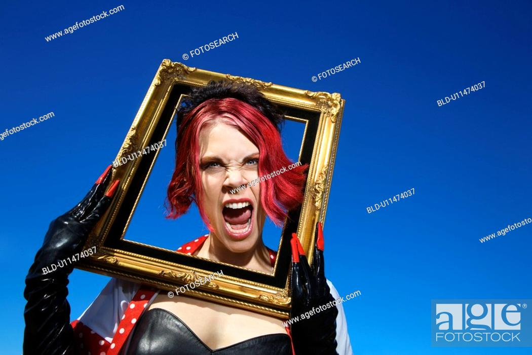 Stock Photo: Young adult Caucasian female holding empty frame around head.