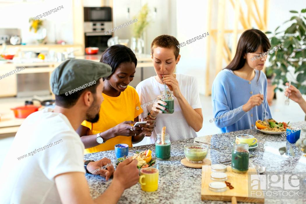 Stock Photo: Friends sitting at kitchen counter eating and drinking.