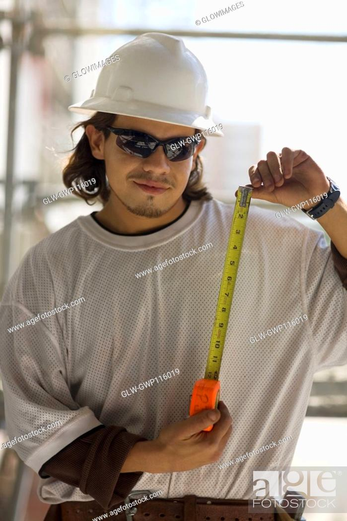 Stock Photo: Young man holding a tape measure.