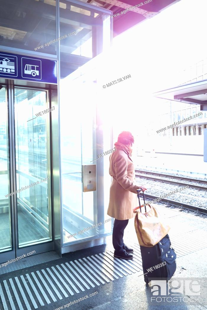 Stock Photo: Woman With Luggage on Railroad Station with Sunlight in St Gallen, Switzerland.
