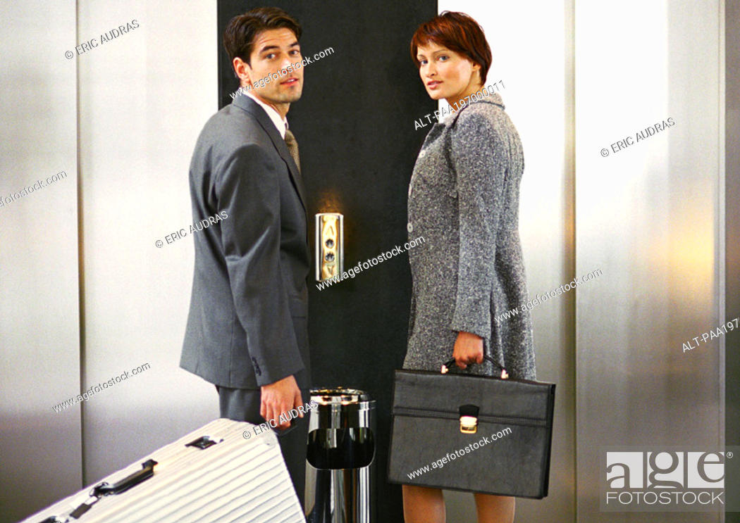 Stock Photo: Businessman and businesswoman waiting for the elevator, looking over shoulders at camera.