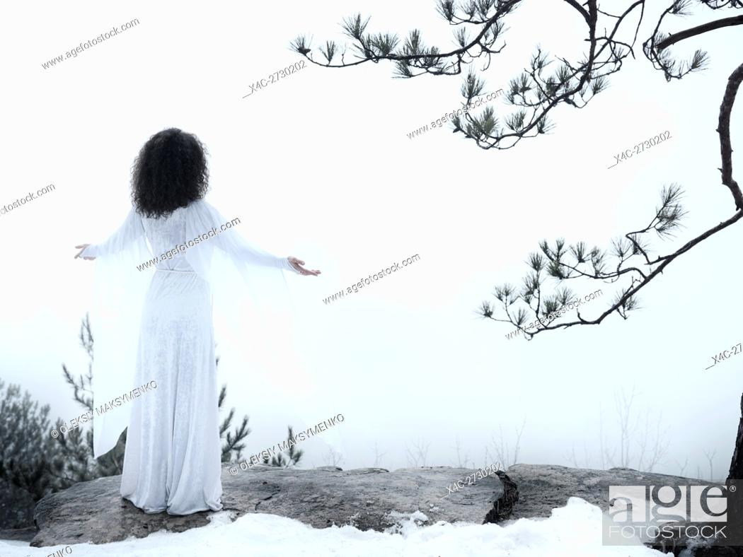 Stock Photo: Woman in white dress standing on a cliff meditating with spread hands embracing the world and the nature. Spiritual concept.