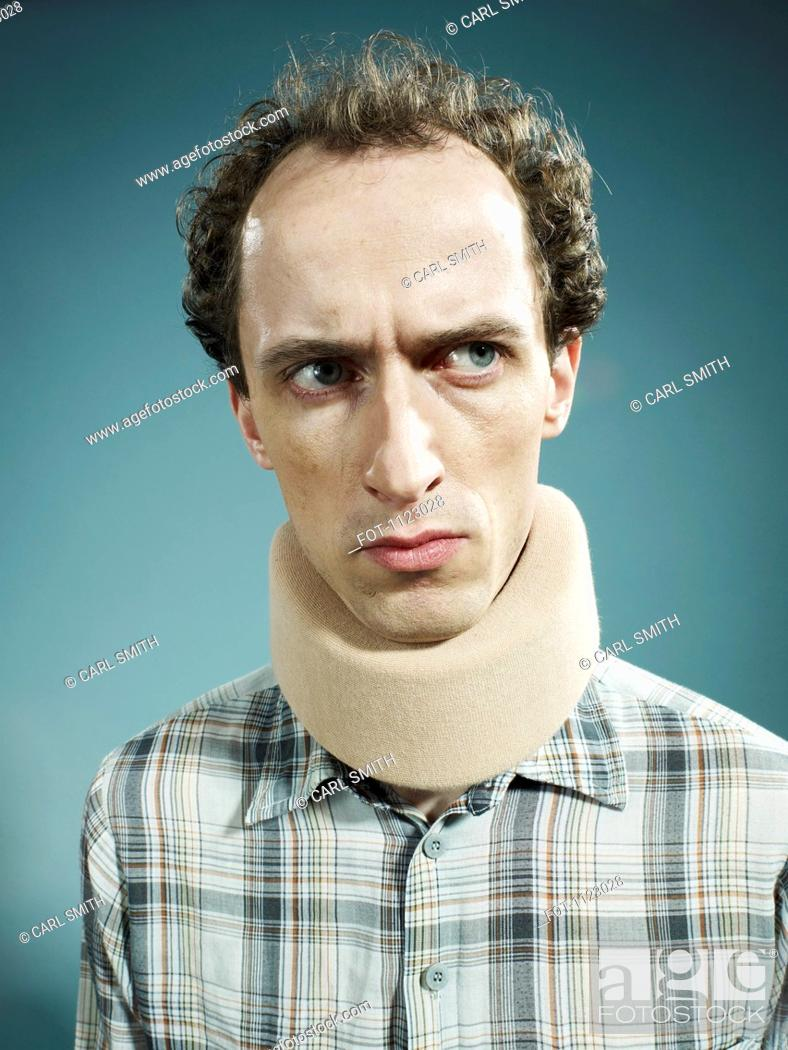 Stock Photo: A displeased man wearing a neck brace and looking suspiciously to the side.