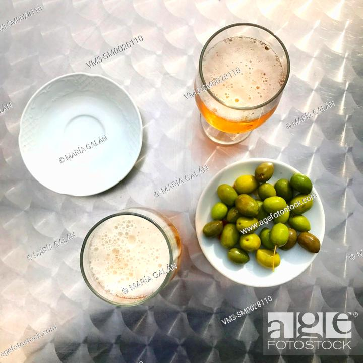 Stock Photo: Two glasses of beer with green olives. View from above.