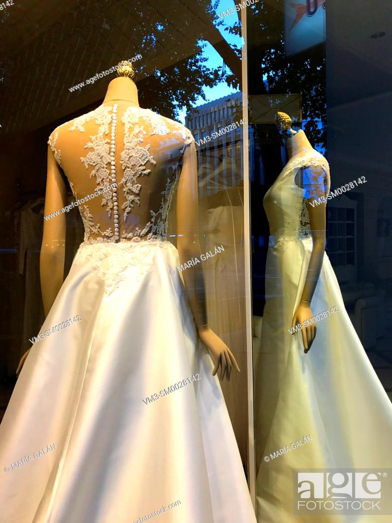 Stock Photo: Wedding dress and its reflection on a mirror in a shop window. Madrid, Spain.