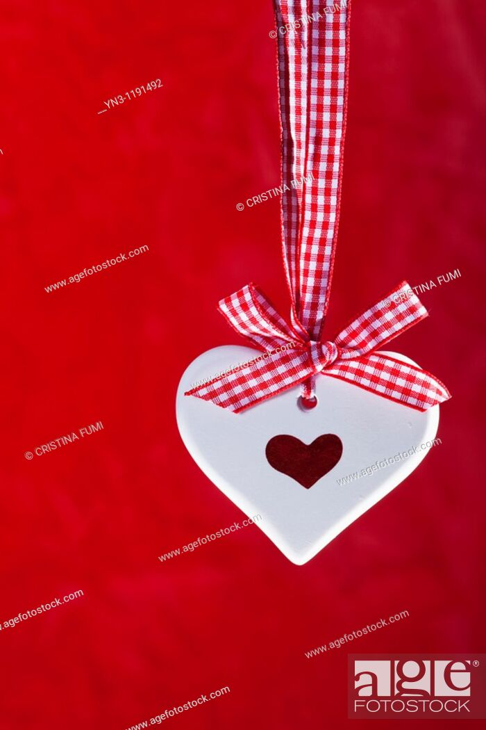 Stock Photo: Scented ceramic heart with red and white ribbon on red background.