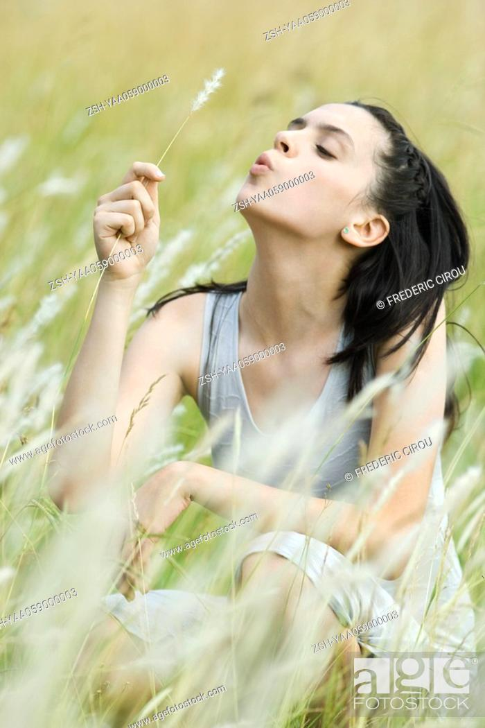 Stock Photo: Teen girl sitting in field, holding sprig of long grass.