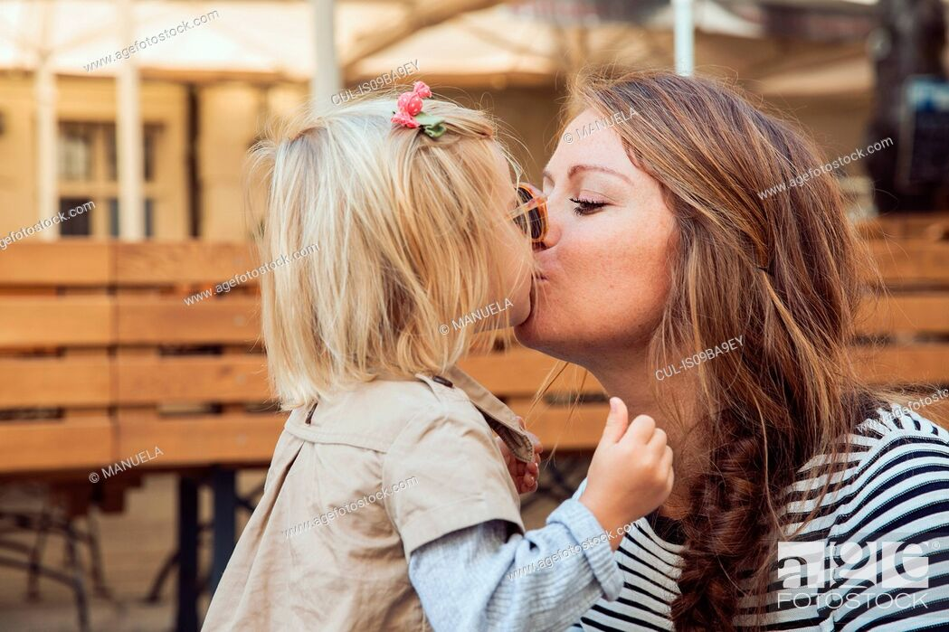 Stock Photo: Mother kissing toddler daughter on park bench.