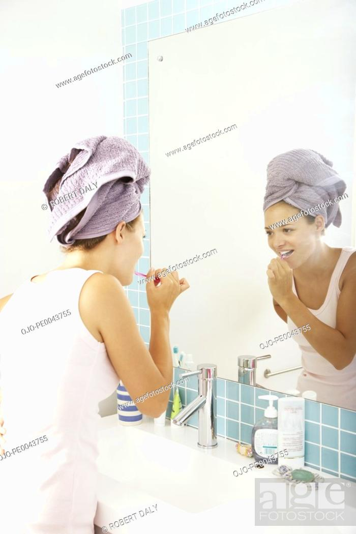 Stock Photo: A young woman brushing her teeth.