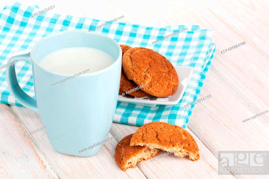 Stock Photo: Cup of milk and gingerbread cookies on white wooden table.