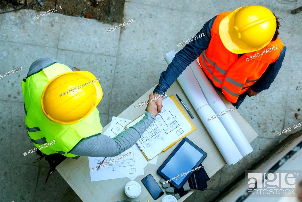 Stock Photo: Woman and man in workwear shaking hands above construction plan.