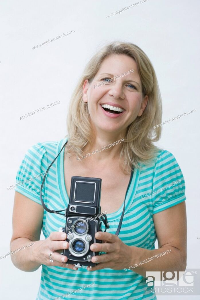 Stock Photo: Portrait of a mature woman holding a camera.