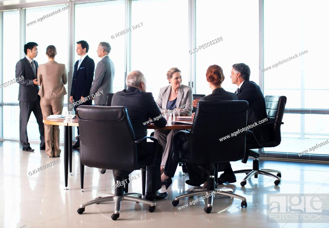 Stock Photo: Business people meeting in separate groups in conference room.