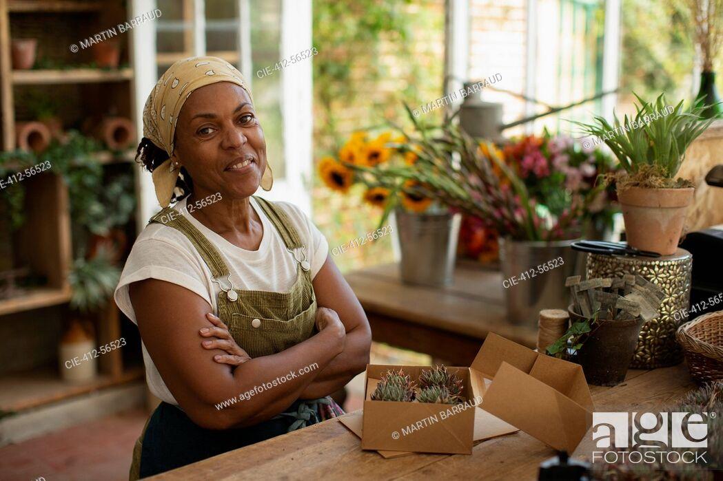 Stock Photo: Portrait confident female florist boxing succulents in shop.